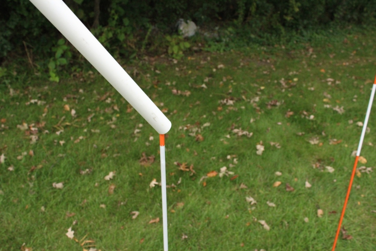 PVC pipes over snowplow stakes for DIY agility weave poles.