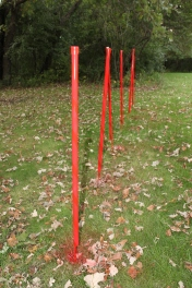 Painting DIY weave poles for training dogs to do agility courses.
